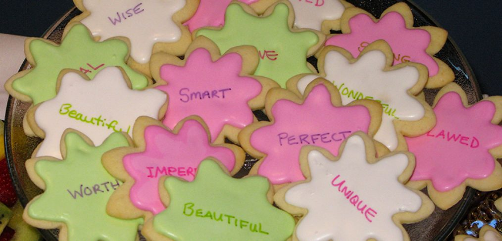 Sugar cookies with empowering messages written on them