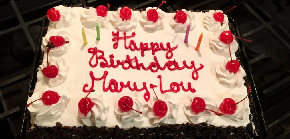 A birthday cake with cherries and candles